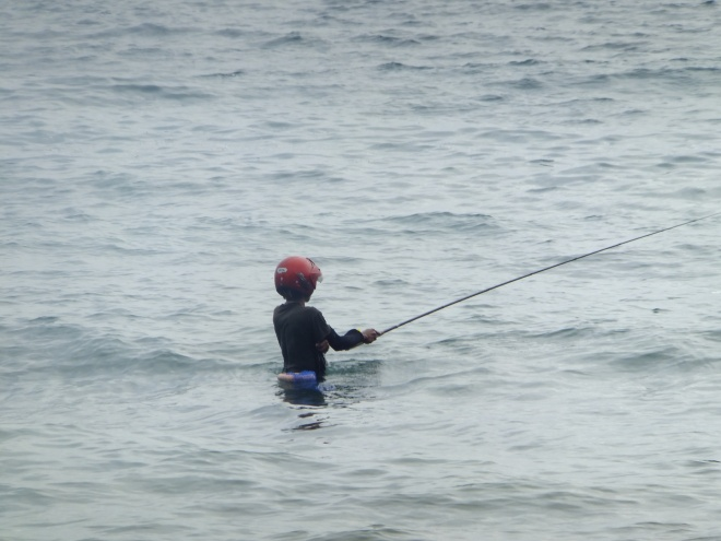 This fisherman is prepared. He's totally protected if a big one he lands hits him in the head!